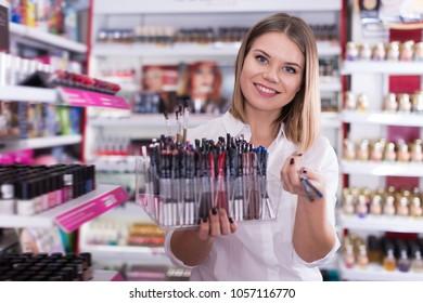 Positive salesgirl suggesting various eyeliners in cosmetics store