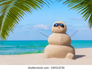 Positive sandy snowman in black sunglasses and carrot nose at tropical ocean beach under palm leaves shade. Happy New Year and Merry Christmas travel destinations for tropical vacations concept