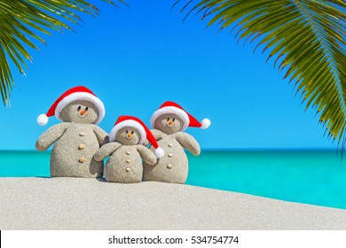 Positive sandy Snowmen family in red Santa hats at sunny ocean tropical palm beach. Happy New Year and Merry Christmas concept for hot travel destinations natural background.