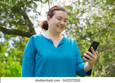 Positive satisfied woman with mobile phone enjoying online chatting. Happy Caucasian lady using smartphone in park and smiling at screen. Connection outdoors concept