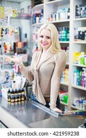 Positive seller at cash register desk in cosmetic shop