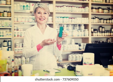 Positive seller recommending skin care products in specialized shop