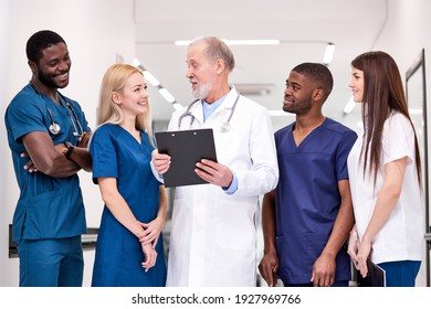 Positive senior doctor in white uniform and young doctors therapists posing looking at camera, elderly man holding clipboard in hospital, multidisciplinary medical team have talk