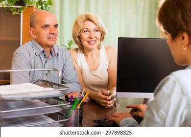 Positive senior female opening saving account in bank