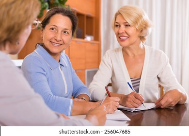 Positive senior ladies signing documents at notary. Focus on brunette
