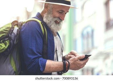 Positive senior male tourist using mobile phone