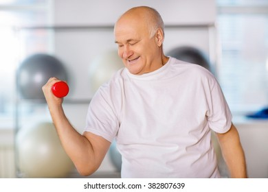 Positive senior man practicing with weights