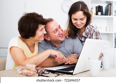 Positive senior man and woman looking at laptop together with their adult daughter indoors. Focus on man