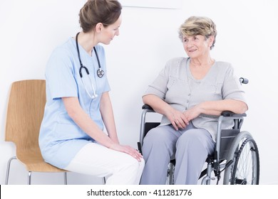 Positive senior with wheelchair and her young doctor sitting in light interior