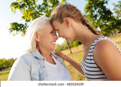 Positive senior woman and her granddaughter standing head to head