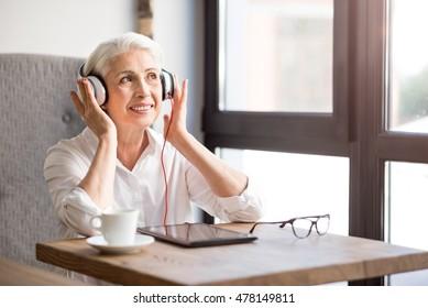 Positive senior woman listening to music