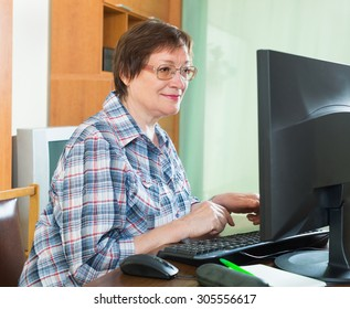 Positive senior woman sitting in front of PC and using keyboard