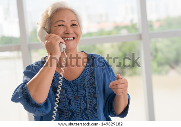 Positive senior woman talking on the phone