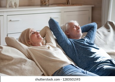 Positive serene mature couple wearing casual clothing lying on comfy sofa putting hands behind heads sleeping or daydreaming. Middle aged spouses wife husband resting in sitting room having day nap