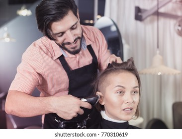Positive sexy adult hairdresser working with hair clipper with woman