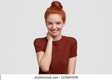 Positive shy ginger girlfriend has tender smile, keeps hand on neck, being in high spirit, rejoices spending free time with boyfriend, poses against white background. Positive emotions concept