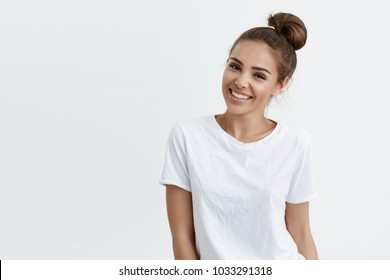 Positive slim european girl with bun hairstyle, smiling broadly while standing over white background, expressing confidence and sensuality. Makeup blogger records new video-tutorial