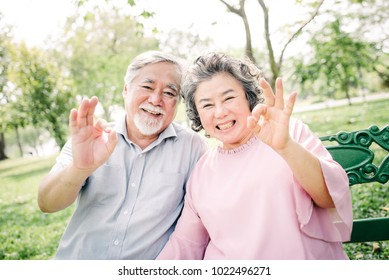 Positive smiing happy Asian senior couple with ok hand sign gesture in the park