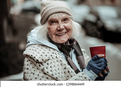 Positive smile. Portrait of a cheerful aged woman smiling to you while being in a great mood
