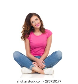 Positive Smile. Young woman in pink shirt and jeans sitting on a floor with legs crossed. Full length studio shot isolated on white.