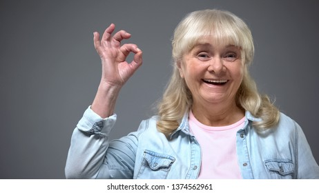 Positive smiling aging female showing ok gesture, governmental aid approval