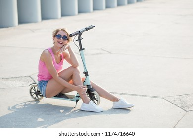 Positive smiling blonde woman sitting at blue kick scooter