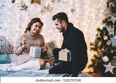 Positive smiling couple opening Christmas gifts while relaxing togetherness in cozy homey interior, carefree male and female in love enjoying winter time indoors, concept of family relationship