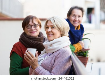 Positive smiling elderly female friends drinking coffee at patio. Focus on blonde
