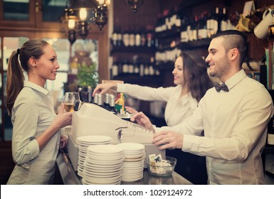 Positive smiling female drinking wine at counter and chatting with bartenders