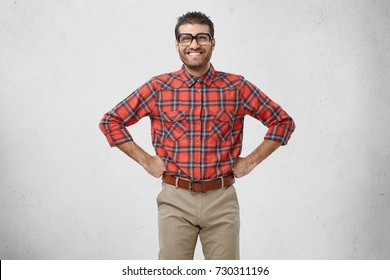 Positive smiling man keeps hands on waist, being confident in his victory. Young clumsy male wonk has happy expression as going to have first date with girlfriend, thinks what flowers to buy