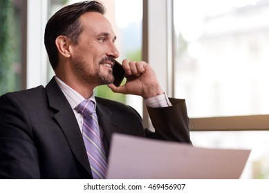 Positive smiling man talking on cell phone