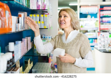 Positive smiling mature female patient buying medicine in pharmacy