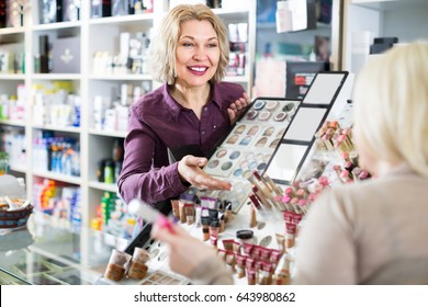 Positive smiling mature female seller near display with cosmetics in beauty store