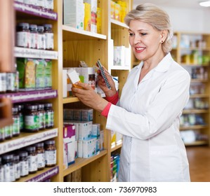Positive smiling mature female seller suggesting useful skin care products in specialized shop