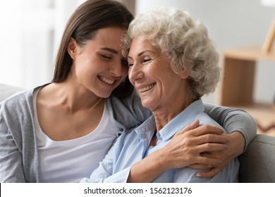 Positive smiling old grandma mother and young adult granddaughter daughter bonding at home, happy two generation women family laughing hugging having fun enjoying time together at reunion meeting