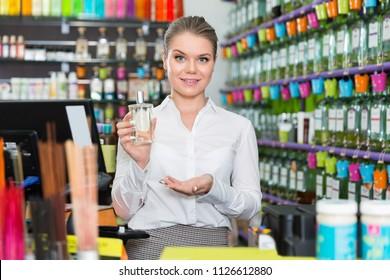 Positive smiling pleasant salesgirl suggesting perfume in modern cosmetic store