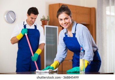 Positive smiling  professional cleaners doing cleanup in ordinary apartment