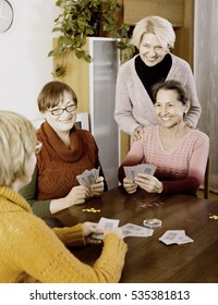 Positive smiling senior female friends playing cards at home