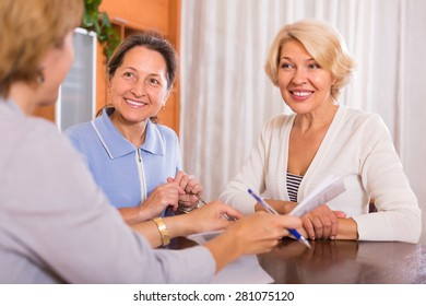 Positive smiling senior ladies signing documents at bank with agent