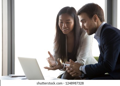 Positive smiling successful diverse multi-ethnic colleagues sitting looking at computer screen, asian businesswoman caucasian businessman discussing feels satisfied working together on new project
