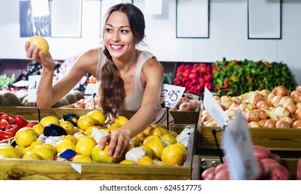 Positive smiling woman buying fresh lemons on marketplace