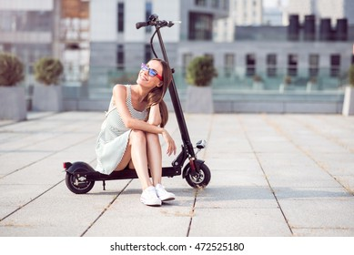 Positive smiling woman riding a kick scooter