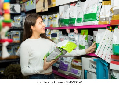 Positive smiling young brunette carefully choosing dry food in pet store