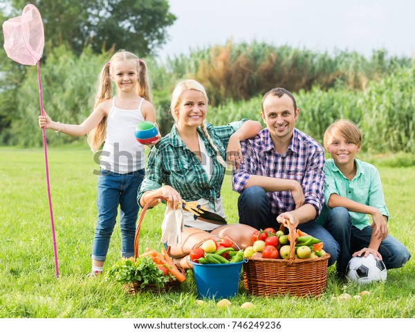 Positive smiling young family with two children at summer picnic at countryside