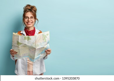Positive smiling young female tourist searches for inspiring places, holds paper map, finds new sightseeing for discovering, wears round spectacles, red bandana, isolated on blue studio wall