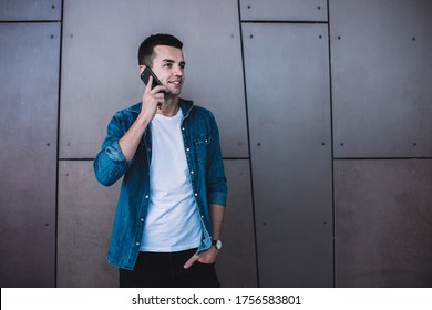 Positive smiling young male in stylish clothes standing outside alone near wall of urban building and speaking on mobile phone