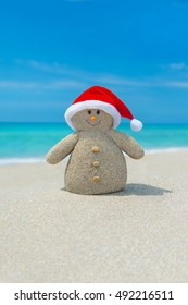 Positive Snowman in red Santa hat at ocean tropical beach. New Year and Christmas destinations for holiday vacation in hot countries concept.