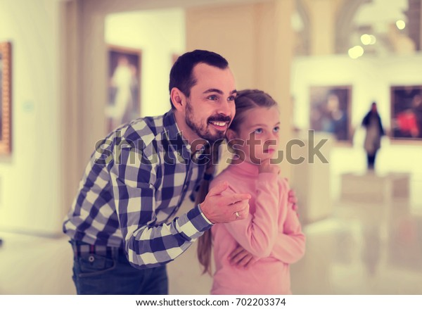 positive spanish father and daughter looking at paintings in halls of museum