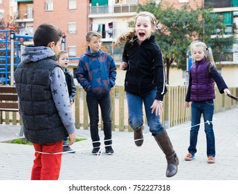 positive spanish kids skipping on chinese jumping elastic rope in yard