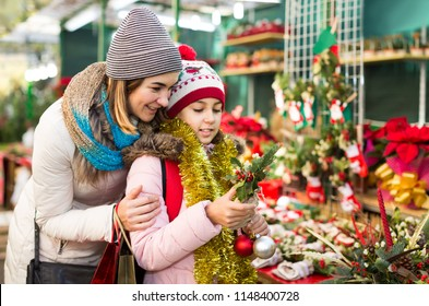 positive spanish  woman with daughter looking at floral decoration at Cristmas fair
